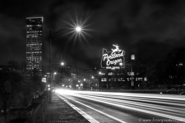 Long exposure photograph of a street of Burnside Street in downtown Portland Oregon at night.