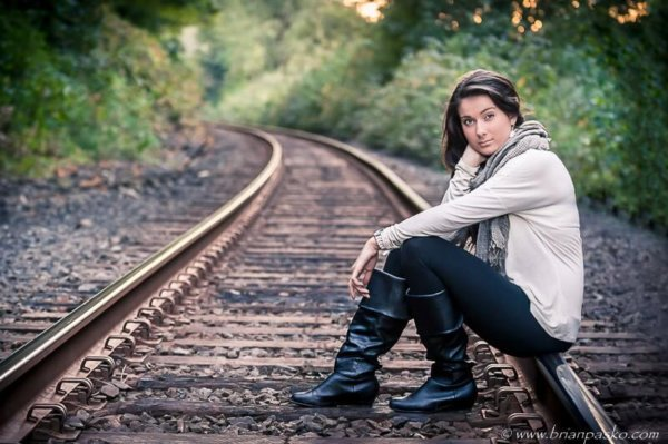 Portrait of a Reynolds High School senior girl with picture sitting on railroad tracks at sunset.