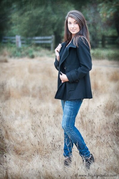 Reyholds High School Senior girl posing in black peacoat with picture in field in Troutdale.