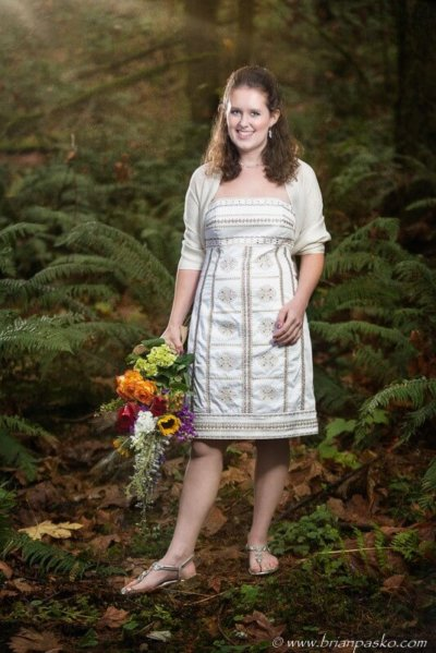 Senior Portrait of a Cleveland High School girl in a white dress picture in forest with bouquet of flowers.