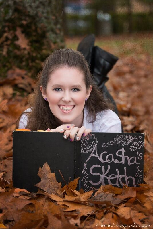 Cute high school senior portrait with girl reading book in fall leaves.