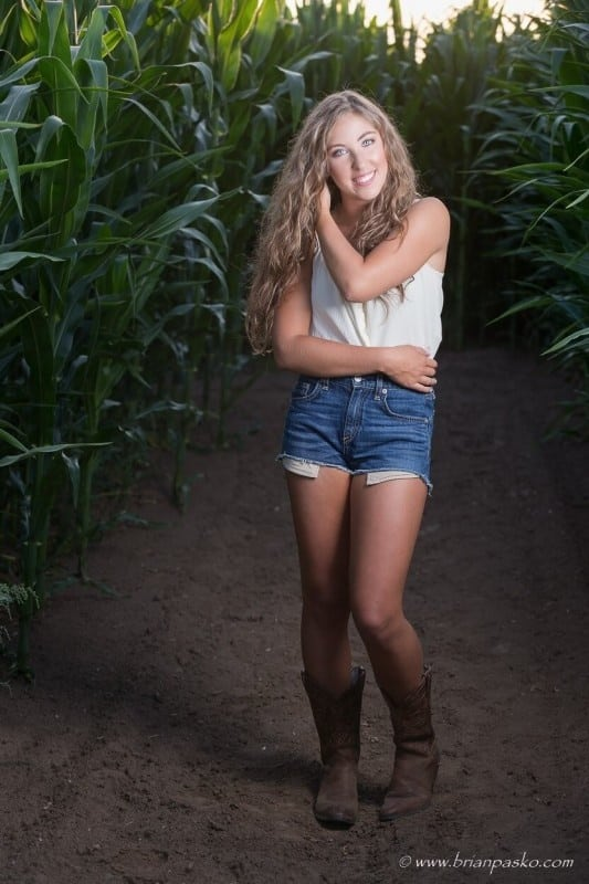 High school senior portrait with cool lighting and picture of girl in corn field.