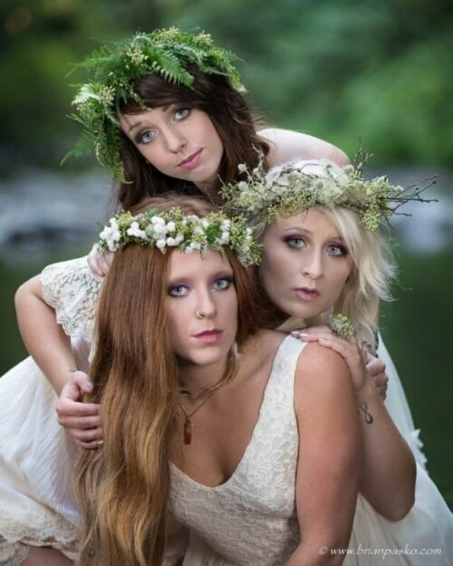 Fashion portrait of three beautiful forest nymphs pictured in a forest wearing floral crowns near a mountain stream.