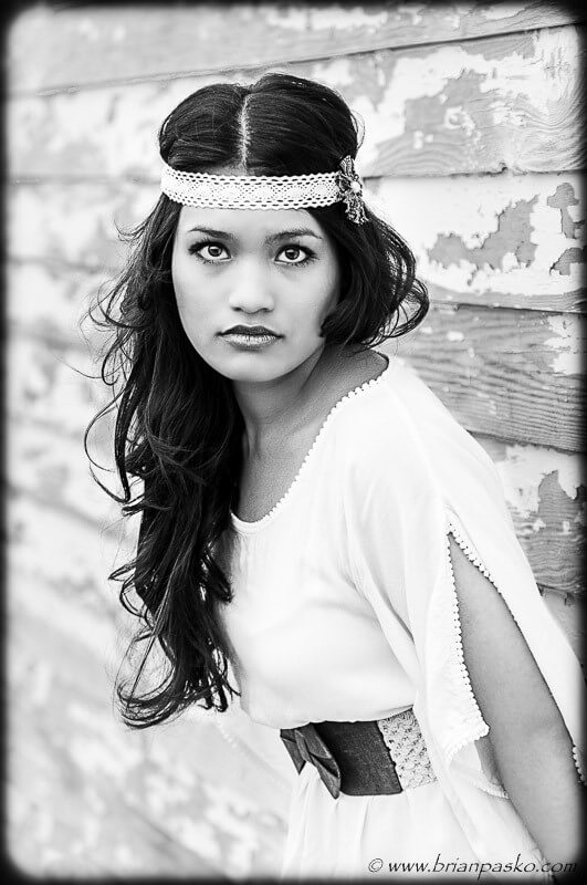 Beautiful black and white high school senior portrait with girl in high fashion outfit.