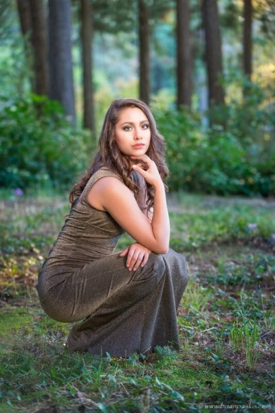 Portrait of a high school senior in a formal sequin dress with warm sunlight picture in woods with vampire diaries theme.