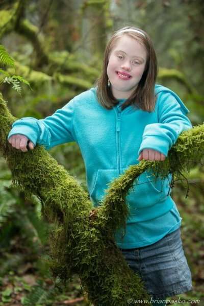 Portrait of a beautiful Estacada High School senior with special needs picture in blue jumper in mossy forest.