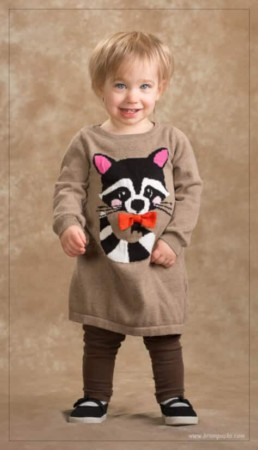 Image of a toddler wearing a racoon sweater taken in studio.