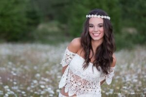 High School senior portrait of girl in boho outfit with white flower headband.