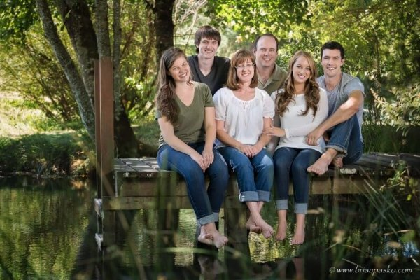 Portrait of an extended family sitting on the dock at a pond in Beavercreek Oregon.
