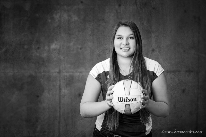 High school senior portrait of girl and volleyball with cool background.
