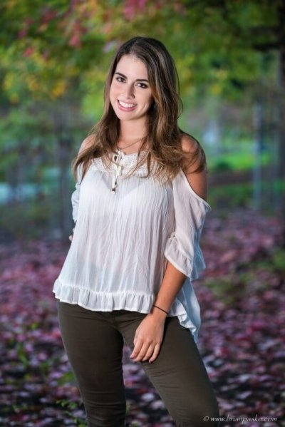 Beautiful portrait of a Sunset High School senior girl picture with autumn foliage and fall colors in Portland park.