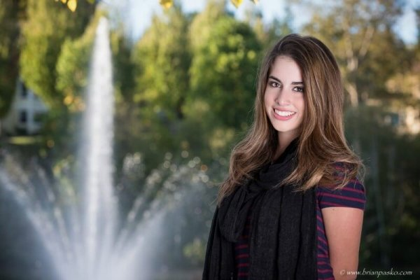 Beautiful portrait of Sunset High School senior girl with picture near fountain in a lake at a Portland park.