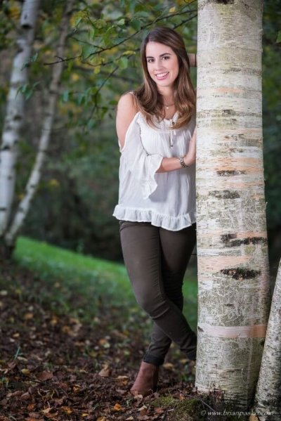 Portrait of Sunset High School senior girl with beautiful picture in woods by birch tree in fall.