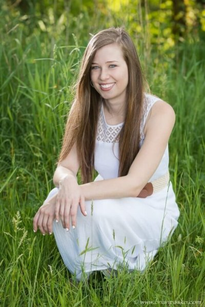 Portrait of a woman in a white dress sitting in lush green grass picture in spring.