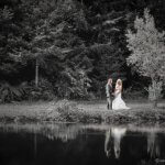 Portrait of a beautiful bride and groom by lake desaturated picture of outdoor wedding in Sandy Oreogn.