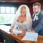 Portrait of a bride and groom signing their wedding license picture at reception in Sandy Oregon.