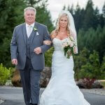 Portrait of father and beautiful bride walking to their outdoor wedding ceremony in Sandy Oregon.