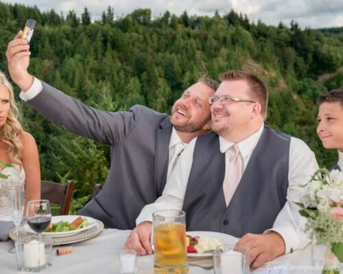 Picture of a groom taking a selfie of his groomsmen at an outdoor wedding reception in Sandy Oregon.