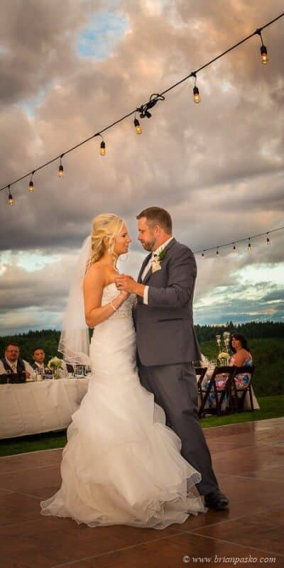Portrait of bride and groom dancing at their wedding reception with picture outdoors in Sandy Oregon with dramatic sky.