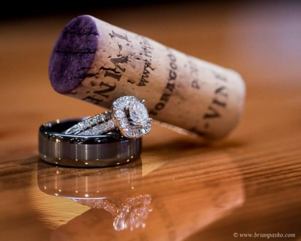 Picture of beautiful wedding rings and a wine cork with reflection on bar table.