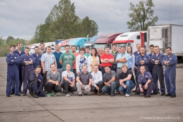 Portrait of the NV Transport Incorporated team picture with company trucks.
