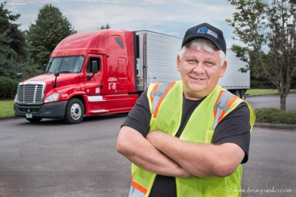 Commercial portrait of a man and truck picture in yellow safety vest.