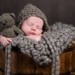 Portrait of newborn baby sleeping in a bucket with picture holding a stuffed teddy bear.