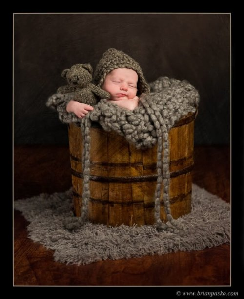 Newborn baby portrait picture sleeping posed in a bucket with teddy bear, knit hat, and braids.