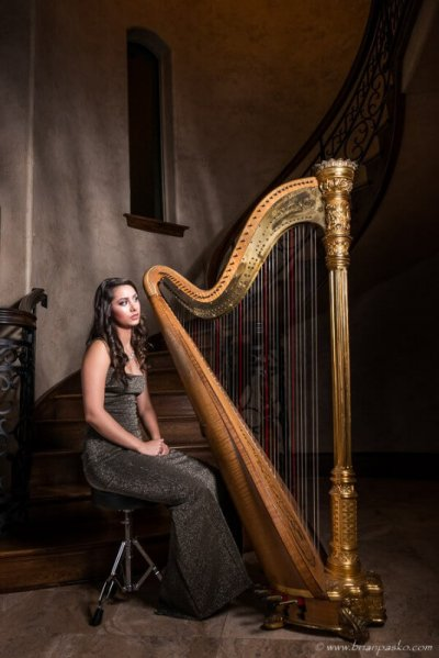 High school senior portrait of a girl in her home picture with golden harp and winding staircase.