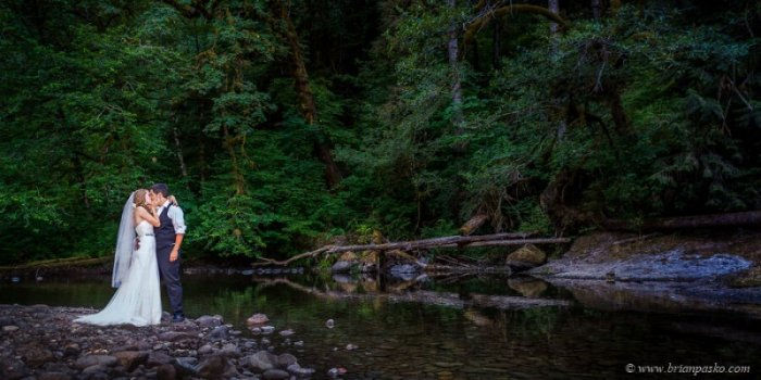 Portrait of beautiful bride kissing groom picture with rocks and mountain stream at Eagle Fern Park in Oregon