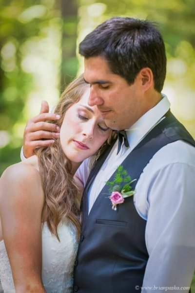 Portrait of a beauiful bride on groom shoulder with outdoor wedding picture at Eagle Fern Park in Oregon.