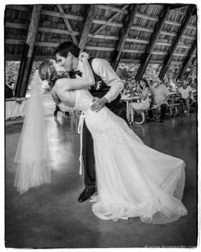 Black and white portrait of a groom dipping bride during first dance at wedding at Eagle Fern Park in Oregon.