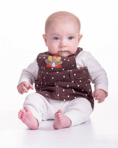 Portrait of a baby picture with a brown thanksgiving jumper with turkey on high key white background.