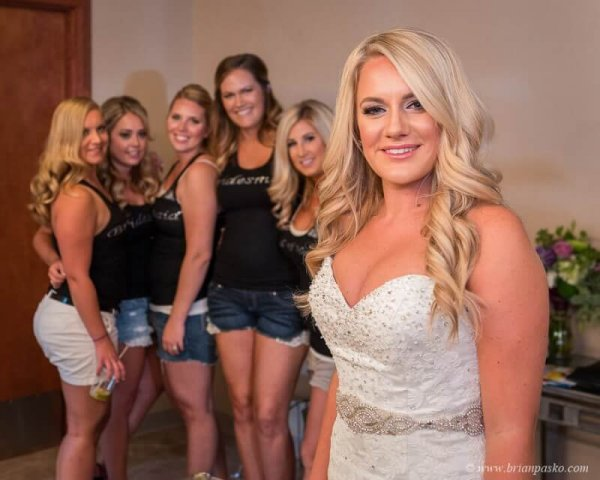 Bridal portrait of bride in dressing room with bridesmaids picture of wedding at Camas Meadows Golf Club in Washington.