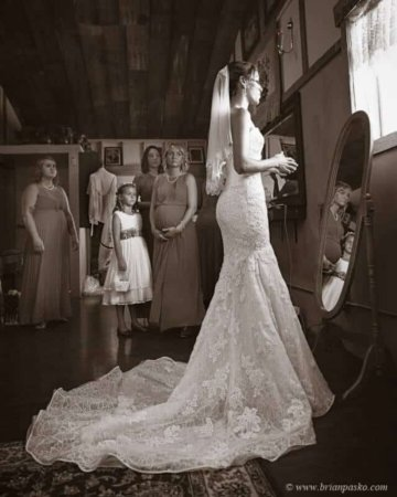 Portrait of beautiful bride in wedding dress getting ready picture of bridesmaids watching at Postalwaits country wedding venue in Canby Oregon.
