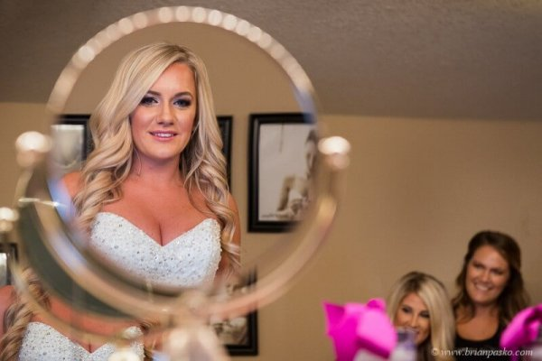 Portrait of a bride looking into makeup mirror with watching bridesmaids picture of wedding at Camas Meadows Golf Club in Washington.