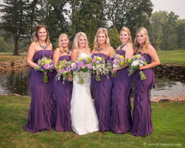 Portrait of Bride and Bridesmaids with purple dresses and bouquets by lake picture of wedding at Camas Meadows Golf Club in Washington.