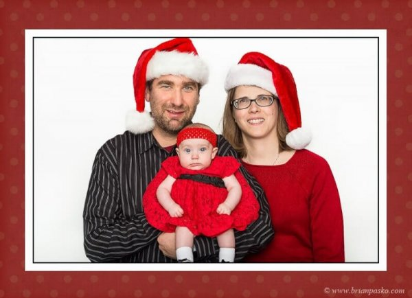 Family portrait and holiday card with mom, dad and baby at Christmas with Santa hats.
