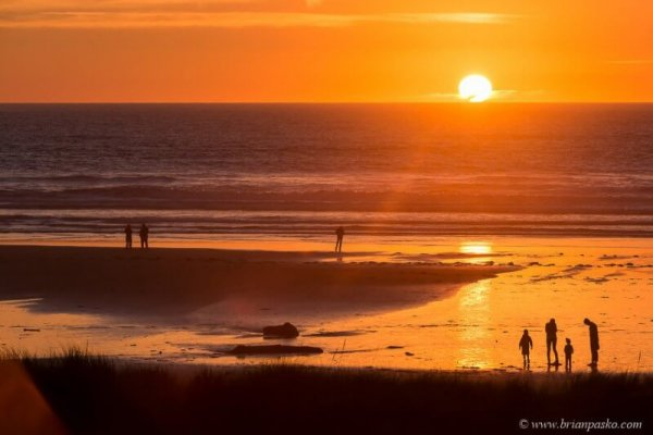 Picture of family silhouette at ocean with blazing sun at sunset in Manzanita Oregon.