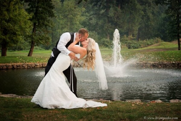 Picture of a groom dippling his bride near fountain with portrait of wedding at Camas Meadows Golf Club in Washington.