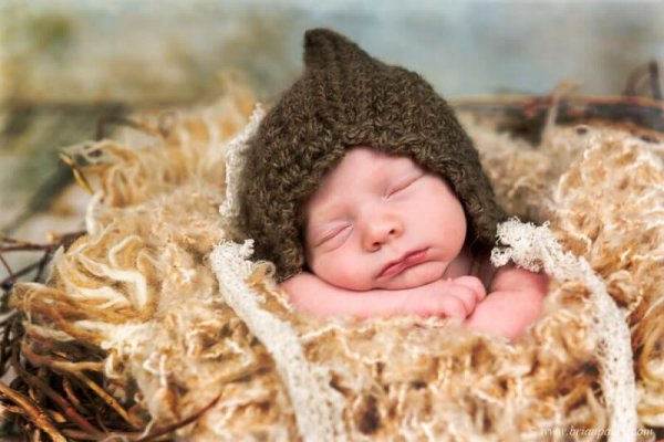 Portrait of a newborn baby with picture in a brown hat sleeping with posed hands.