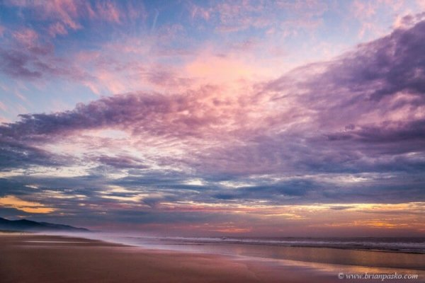 Picture of colorful sunset with sand and ocean in Manzanita Oregon.