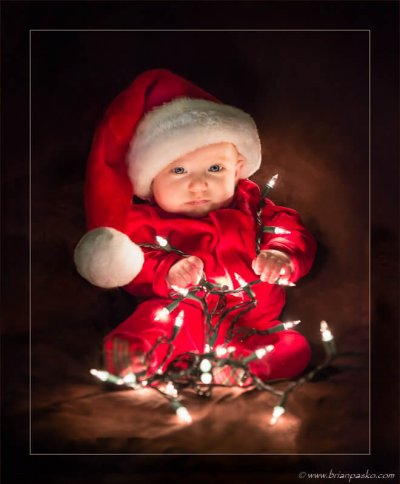 Baby in a santa hat and red pajamas wrapped in holiday Christmas lights with beautiful soft lighting.