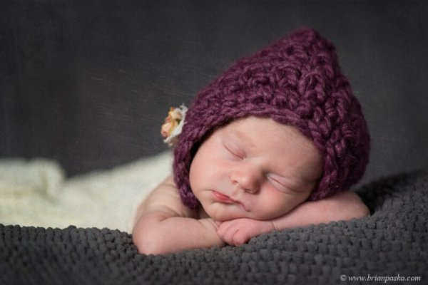 Portrait of a sleeping newborn baby picture in a white cloth and posed in purple knit hat.