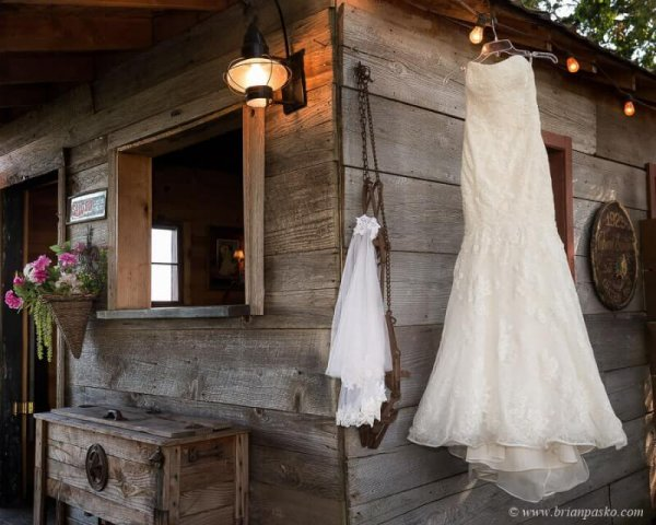 Picture of a wedding dress hanging in a rustic antique barn setting at Postalwaits country wedding venue in Canby Oregon.