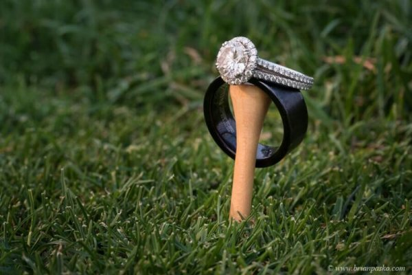 Picture of wedding rings on green grass and golf tee at wedding at Camas Meadows Golf Club in Washington.