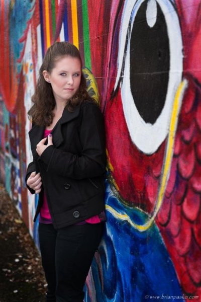 Artistic portrait of a high school senior girl with picture against a colorful mural.