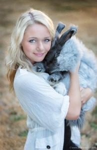 Creative high School senior portrait of a girl in stylish outfit with her pet rabbit.