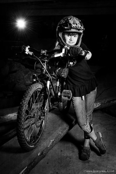 Black and white portrait of a young girl picture with helmet and mountain bike.