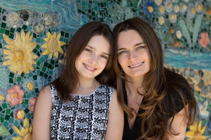 Family portrait of mother and young daughter picture with colorful tile background at elementary school.
